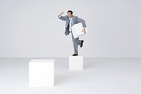 Businessman holding pedestal block, shaking fist