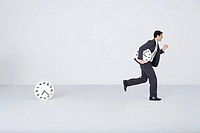 Businessman running with clock, leaving second clock behind