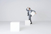 Businessman carrying block, stepping onto larger block