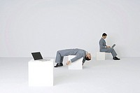 Identical businessmen, one using laptop while the other lies on back, exhausted