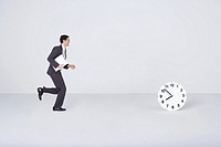 Businessman running toward clock
