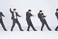Identical businessmen playing tug-of-war for the same side (thumbnail)