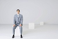 Businessman sitting on block, smiling at camera