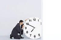 Businessman staring at oversized clock
