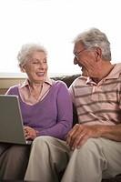 Smiling couple using laptop