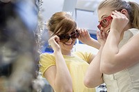 Teen girls trying on sunglasses