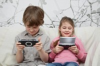 Brother and sister using hand_held video games
