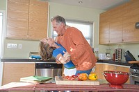 Middle_aged couple dancing in kitchen