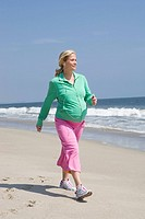 Pregnant woman power walking on beach