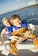 Smiling boy and girl with crab