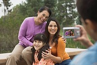 Man taking picture of grandmother, mother, and girl