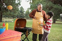 Grandfather and granddaughter with grill