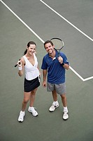 Man and woman holding tennis racquets