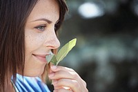 Woman smelling sage leaves