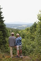 Man and woman looking over forest