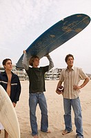 Teenage boys on beach with surfboard