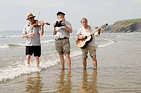 Three traditional acoustic folk musicians playing music on the beach and paddling in the sea at Druidston Haven, Pembrokeshire Coast National Park, WA...