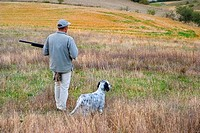 Hunter with his hunting dog in the field, Larraona, Navarra, Spain