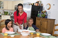 Mother serving spaghetti to children