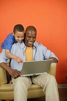 Father and son using laptop computer