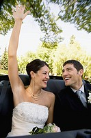 Bride and bridegroom riding in convertible