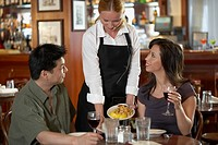 Waitress and couple in restaurant