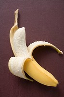 Banana, half peeled, on brown background