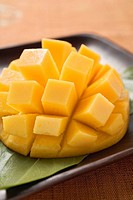 Diced mango still attached to the skin on brown plate