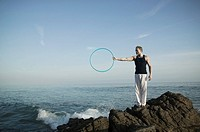Man holding hoop on rocky coast