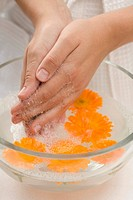 Woman washing her hands in soapy water with marigolds