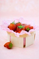 Strawberries in and beside a punnet lined with paper