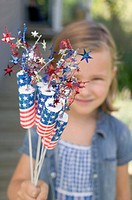Small girl holding 4th of July decorations USA