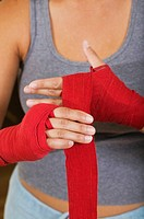 Woman wrapping bandage around hand
