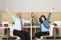 Coworkers with trophy celebrating