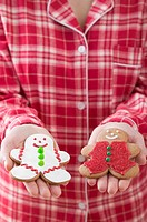 Woman holding two gingerbread men