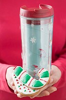Woman holding candy cane biscuits and insulated beaker