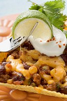 Chili con carne in corn shell, lime on fork Mexico