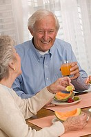 Couple eating cantaloupe and drinking juice