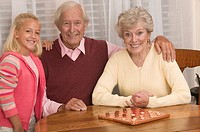 Grandparents playing checkers with granddaughter