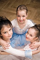 group of three young ballet dancers in close embrace