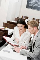 businesswoman and male colleague at restaurant reading document