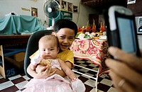 Father takes photo of children with camera phone, Phnom Penh, Cambodia