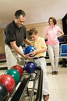 Father helping son with bowling ball