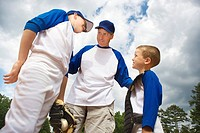 Coach standing between two young baseball players
