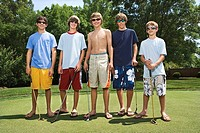 Teenage boys posing on putting green with golf clubs