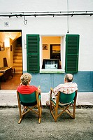 Couple watching the TV on the street, Es Migjorn Gran. Minorca, Balearic Islands, Spain