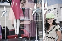 Young woman smiling in front of a clothing store