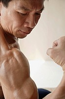 Profile of man flexing muscles