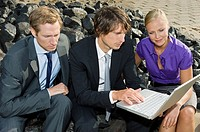 Businesspeople Using Laptop at Beach
