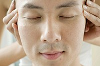 Young man receiving head massage, eyes closed, close-up